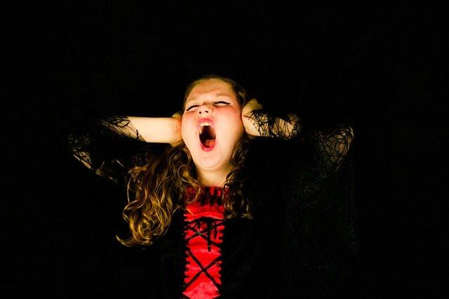 Mustiin ja punaiseen paitaan pukeutunut pitkähiuksinen, meikattu tyttö pitää käsiä korvillaan ja huutaa