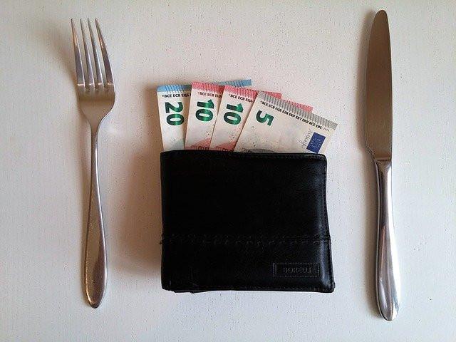 Haarukka, veitsi ja lompakko seteleineen esittää lautasta