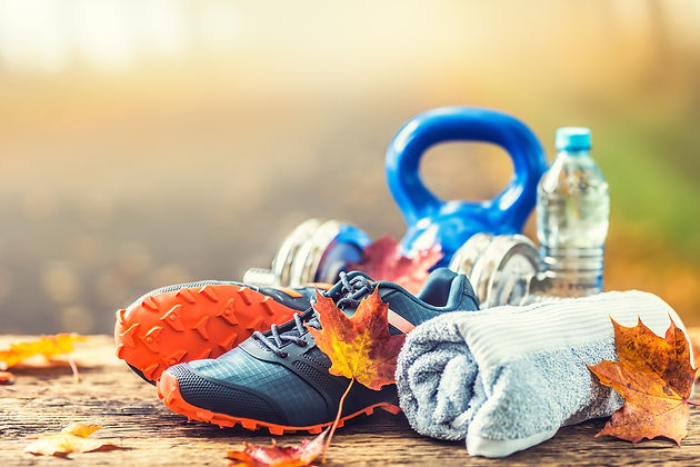 Pair of blue sport shoes water and  dumbbells laid on a wooden board in a tree autumn alle