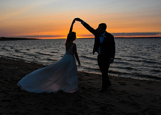 Bride and groom dancing on the beach at sunset