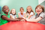 teacher-and-children-with-hands-together