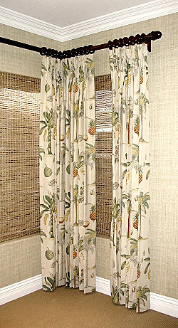 Draperies on deco rod with rings over woven wood shades