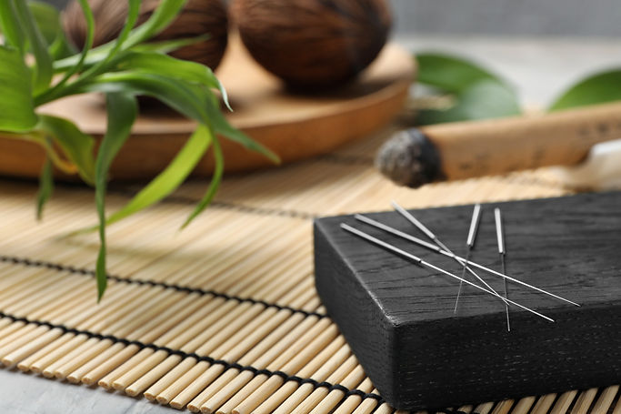 Silver acupuncture needles on black wood