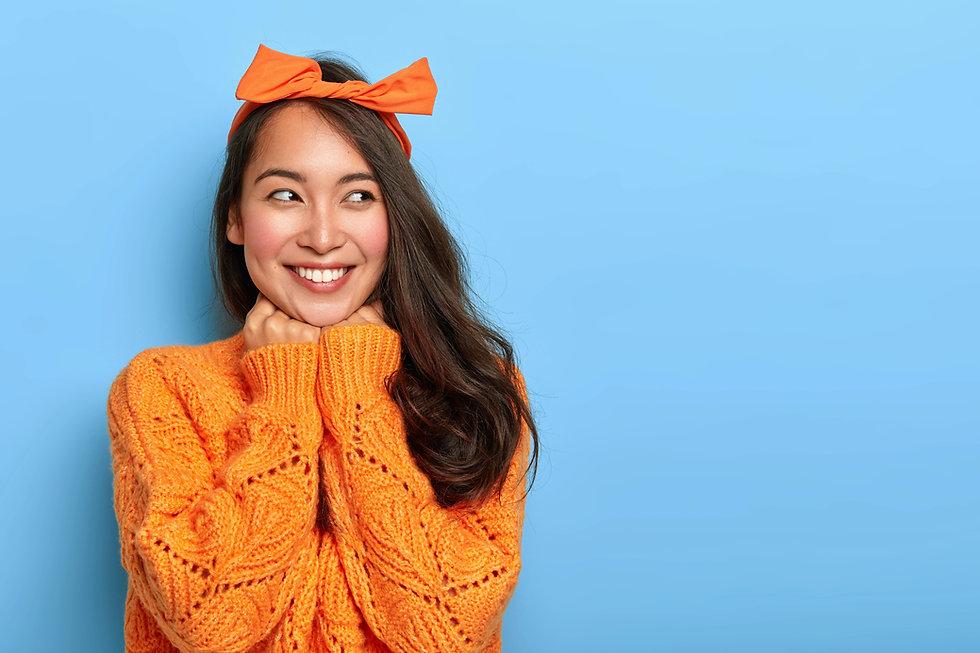 studio-shot-happy-upbeat-woman-wears-bright-orange-knitted-jumper-bow-headband-holds-hands