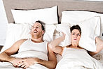 A woman blocking ears while man snoring
