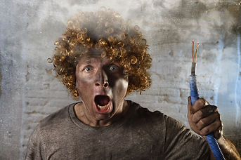 man with funny wig holding electrical ca