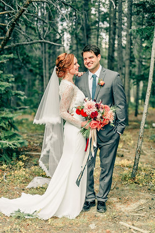 Bride and Groom on their wedding day at Ten Mile Station in Breckenridge Colorado. Bride holding a bouquet of dalias, garden roses, ranunculus, and foliage, wth trailing ribbons. The bouquet is in shades of blush, peach, red, and coral.
