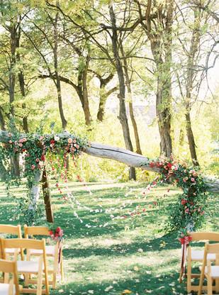 Emma Lea Floral- Purple Summer Events- Tara Bielecki Photography- Lyons Farmette Colorado Wedding   | Ceremony Backdrop | Colorful Greenery and Floral Installation | Outdoor Wedding | Paper Garland | Garden Rose | Dahlia | Orgainc Anthropologie Inspired Backdrop|