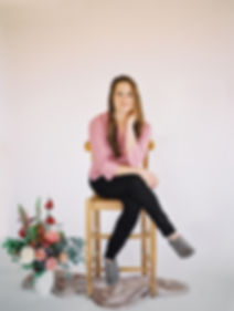 Headshot of the owner and lead designer of Emma Lea Floral on a stool with a fower arragement
