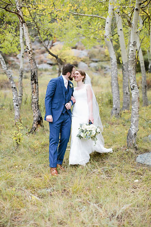 Bride and Groom on their wedding day in fall at Dell Terra Mountain Chateau in Estes Park Colorado. Bride is holding her bouquet of greenery and white flowers designed in Emma Lea Floral's signature lush and textural style