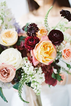 Fine art image of a bridal bouquet designed in Emma Lea Florals signature lush and textural style and created with garden roses, ranunculus,lilac, scabiosa, and lysimacha