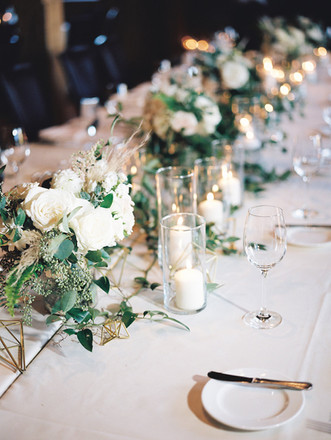 Emma Lea Floral- Purple Summer Events- Kristen Pierson Photography- Devils Thumb Ranch Colorado Wedding  | Candles In Glass Centerpiece | Smilax Greenery | Geode Table Number | Geometric Details | Head Table | Greenery and White Flowers |