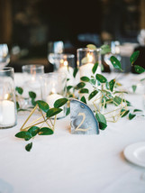 Emma Lea Floral- Purple Summer Events- Kristen Pierson Photography- Devils Thumb Ranch Colorado Wedding | Candles In Glass Centerpiece | Smilax Greenery | Geode Table Number | Geometric Details |