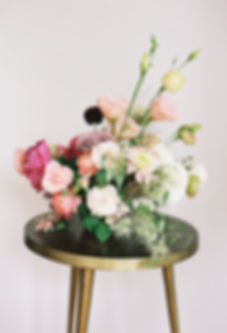 Colorful Fine Art Floral Ceneterpiece deigned by Emma Lea Floral on a gold table featuring garden roses, lisianthus, and ranunculus, in shades f burgundy, pink, blush, mauve, coral, and gold.