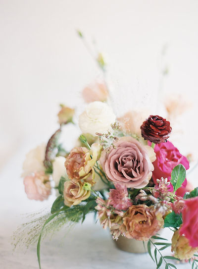 Colorful Fine Art Floral Ceneterpiece deigned by Emma Lea Floral with garden roses, lisianthus, and ranunculus, in shades f burgundy, pink, blush, mauve, and gold.