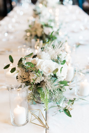 Emma Lea Floral- Purple Summer Events- Kristen Pierson Photography- Devils Thumb Ranch Colorado Wedding    Candles In Glass Centerpiece   Smilax Greenery   Geode Table Number   Geometric Details   Head Table   Greenery and White Flowers  