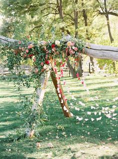 Emma Lea Floral- Purple Summer Events- Tara Bielecki Photography- Lyons Farmette Colorado Wedding  | Ceremony Backdrop | Colorful Greenery and Floral Installation | Outdoor Wedding |  | Ceremony Backdrop | Colorful Greenery and Floral Installation | Outdoor Wedding | Paper Garland | Garden Rose | Dahlia | Orgainc Anthropologie Inspired Backdrop|