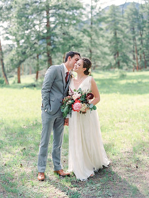 bride and groom in Estes Park at the Della Terra Mountain Chateau venue on their wedding day. The bride is holding a bridal bouquet designed in Emma Lea Floral's signature lush and textural style. Bouquet in shades of ivory, blush, pink, and burgundy, with peonies, garden roses,scabiosa, lysimachia, and foliage.