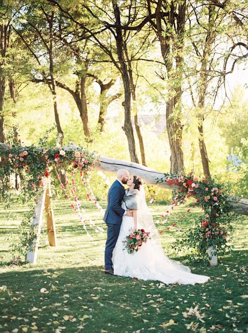 Emma Lea Floral- Purple Summer Events- Tara Bielecki Photography- Lyons Farmette Colorado Wedding   | Ceremony Backdrop | Colorful Greenery and Floral Installation | Outdoor Wedding | Paper Garland | Garden Rose | Dahlia | Orgainc Anthropologie Inspired Backdrop| Bride & Groom |