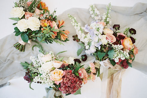 Fine art image of 3 bridal bouquets in a mix of style, all designed in Emma Lea Floral's signature lush and textural style, using garden roses, ranunculus, lilac, lysimachia, scabiosa, hydrangea, and delphinium