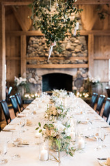 Emma Lea Floral- Purple Summer Events- Kristen Pierson Photography- Devils Thumb Ranch Colorado Wedding  | Candles In Glass Centerpiece | Smilax Greenery | Geode Table Number | Geometric Details | Head Table | Hanging Geometric Shapes With Greenery and Floral Detail |