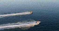 Two jetskis speeding across the water in