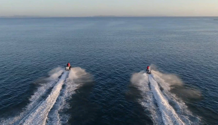 Rear aerial shot of two jetskis heading