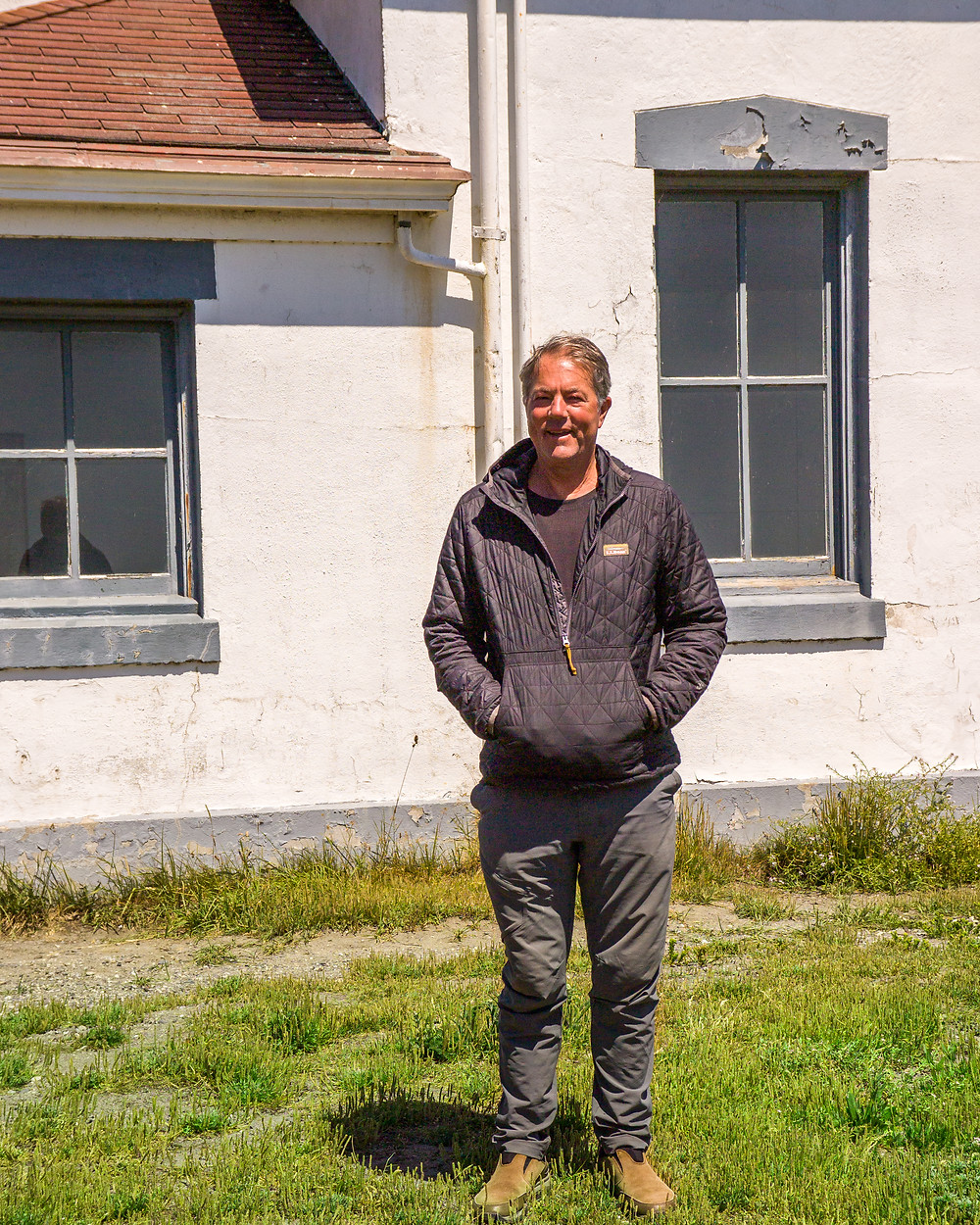 Photo of Jim Angell standing next to the Point Wilson Lighthouse