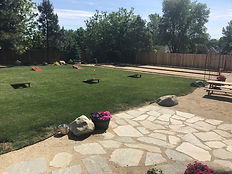 A picture of the backyard showing large grass area, Bocce area and cornhole game boards