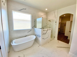Stand alone tub with full marble wall