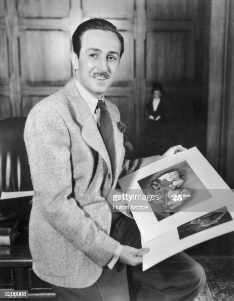 circa 1942: A portrait of American cartoonist and producer Walt Disney (1901 - 1966) seated on the edge of a desk in an office holding illustrations from his animated films 'Snow White and the Seven Dwarfs' and 'Bambi.' Animator David Hand directed both films. (Photo by Hulton Archive/Getty Images)