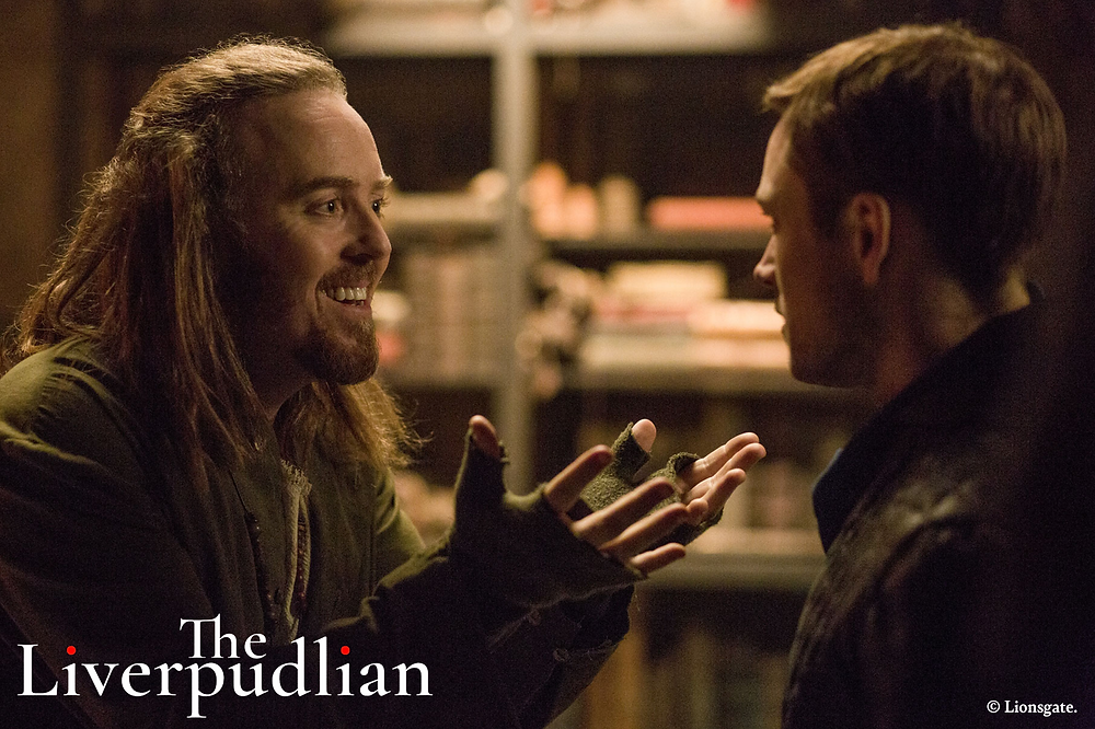 Taron Egerton as Robin Hood in conversation with Tim Minchin as Friar Tuck (Credit: Lionsgate).