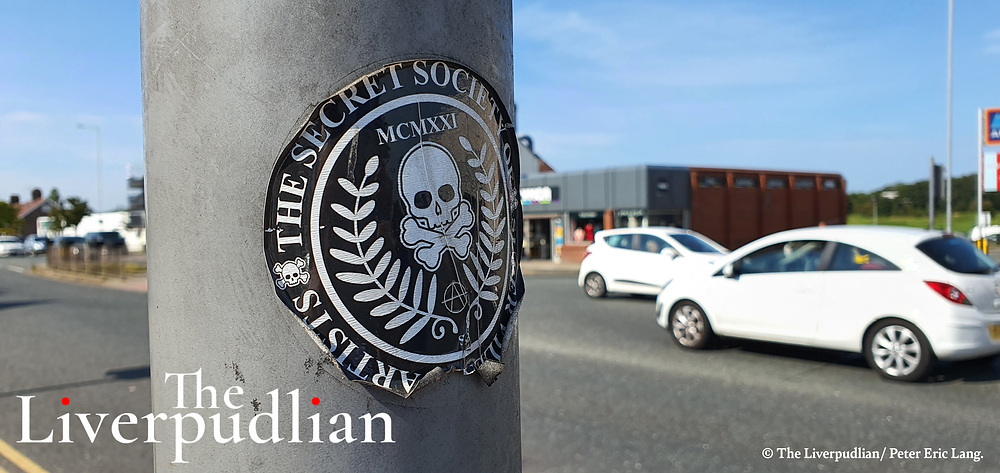 A 'Secret Society of Super Villain Artists' sticker on a lamp post at the junction outside of the Prenton YMCA charity shop (Credit: The Liverpudlian/Peter Eric Lang).