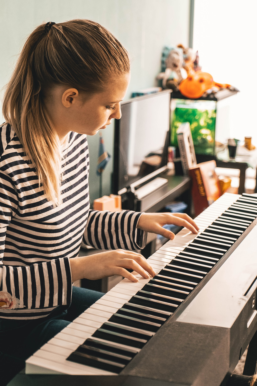 Young woman playing a keyboard at her home
