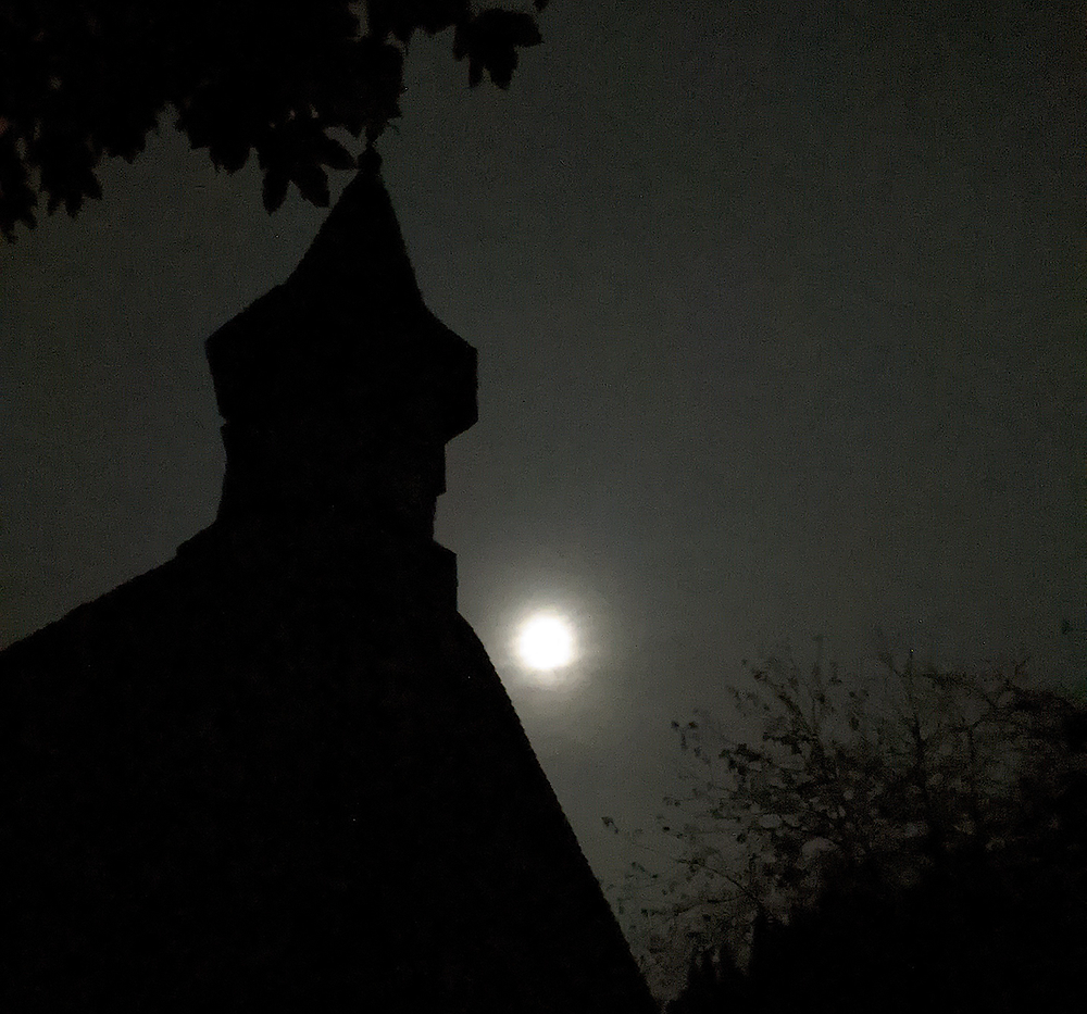 Photo of a misty moon behind a church steeple at night.
