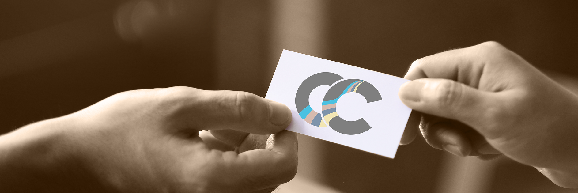 Two hands exchanging a business card with a CC logo on it.