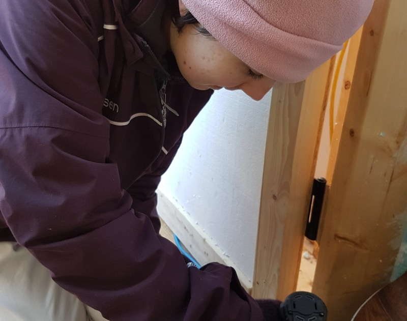 Student installing a dividing board between the propagation room and the cold frame in the greenhouse