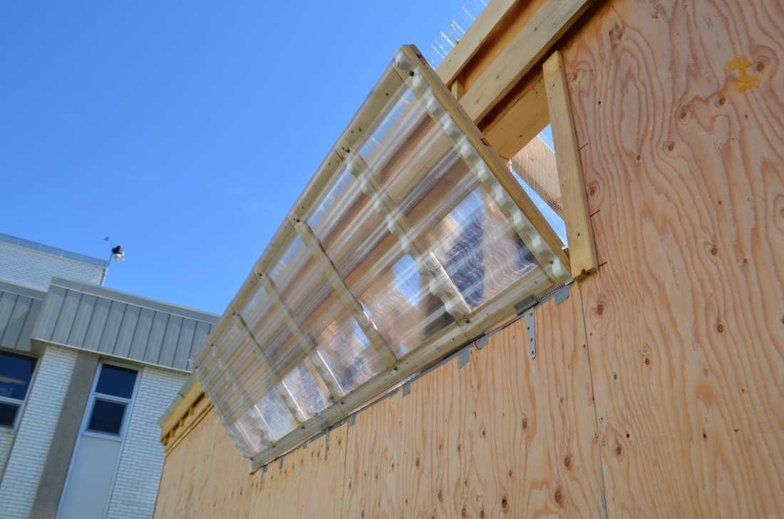 "Solar Powered ""Gigavent"" used for airflow in the back of the greenhouse. This device uses mineral wax to open our back vent, and can lift up to 65 lbs! We are able to manually set opening temperatures between 65 degrees to 75 degrees Fahrenheit, with the vent fully extended at 90 degrees Fahrenheit."