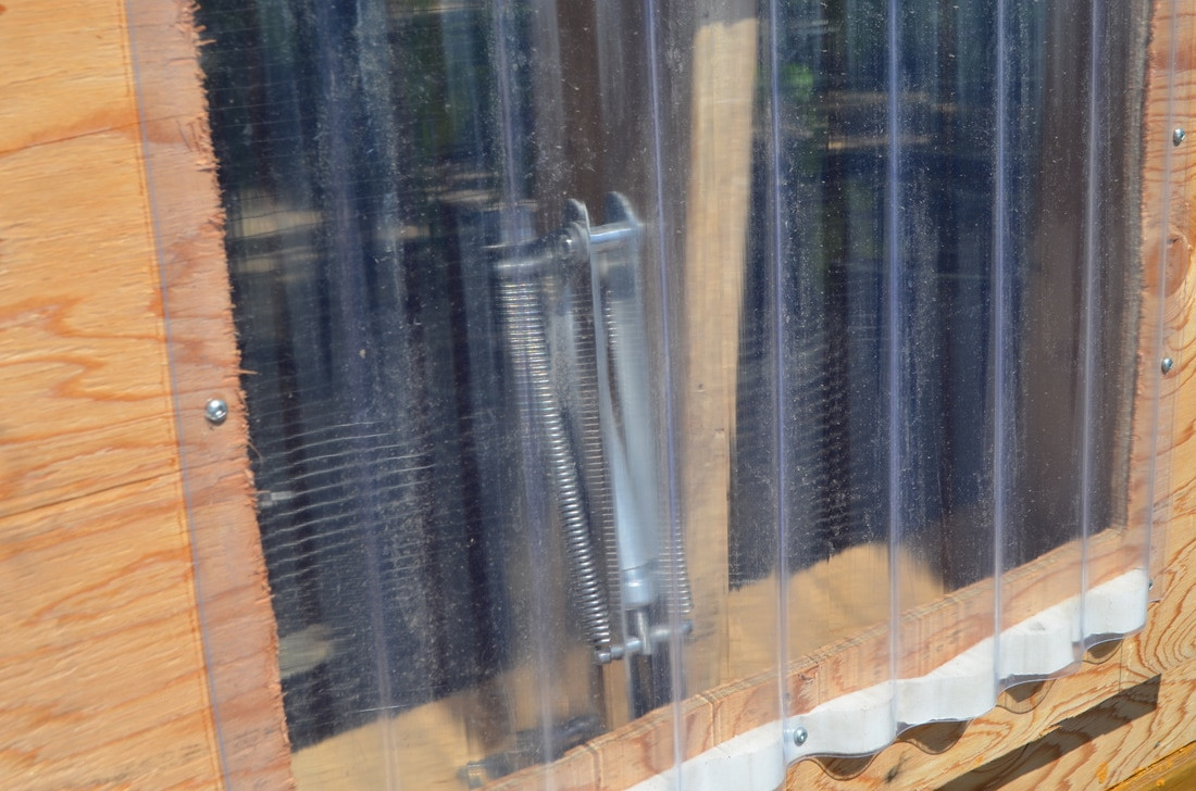 """Solar Powered """"Megavent Storm"""" used for airflow in the front of the greenhouse. This device uses mineral wax to open our front vent. We are able to manually set opening temperatures between 65 degrees to 75 degrees Fahrenheit, with the vent fully extended at 90 degrees Fahrenheit."""