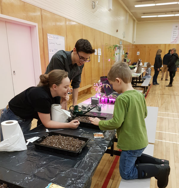 Students from the Sir James Dunn Academy Student-Led Environmental Efficiency Committee (SLEEC) educating local community members at the Environmental Science Night exhibition at Vincent Massey Elementary School.