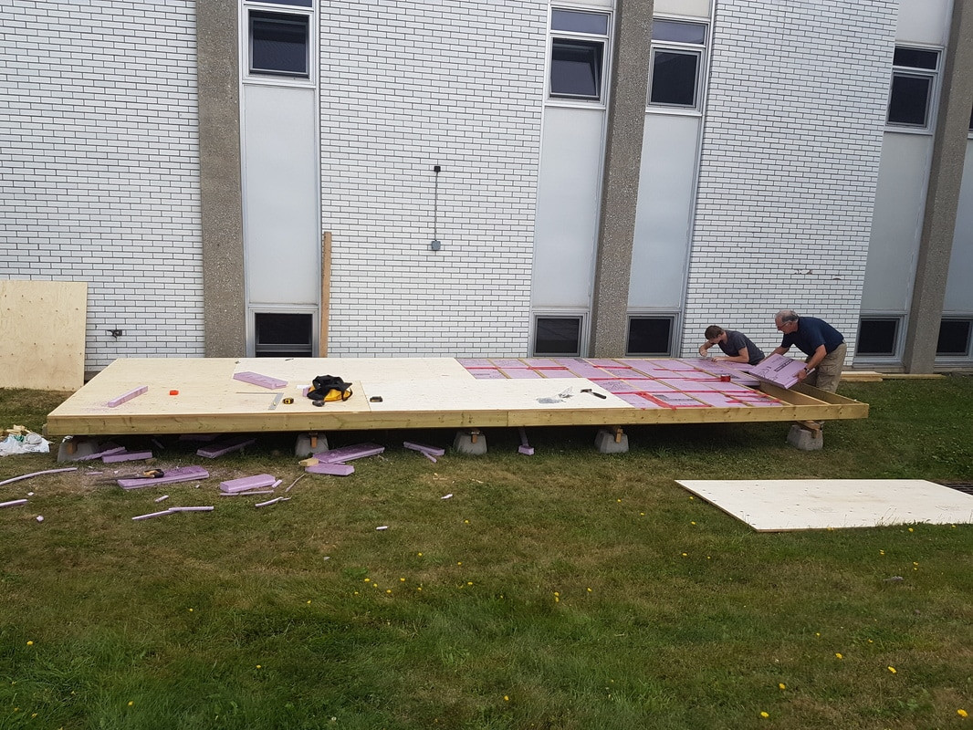 Local community member and volunteer, Tim Stuart, building the greenhouse floor with a student