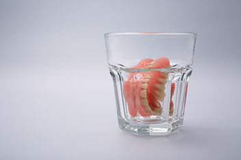 A set of dentures in a glass of water on