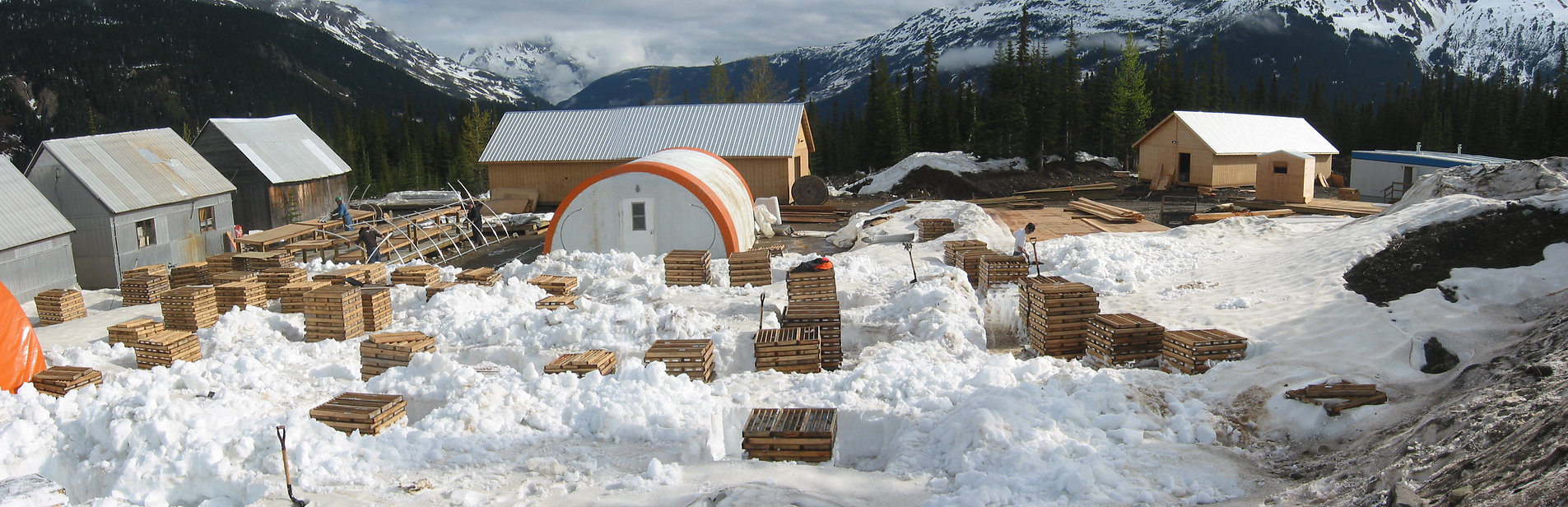 Stacks of drill core in springtime emerging from snow in a mountain mineral exploration camp.