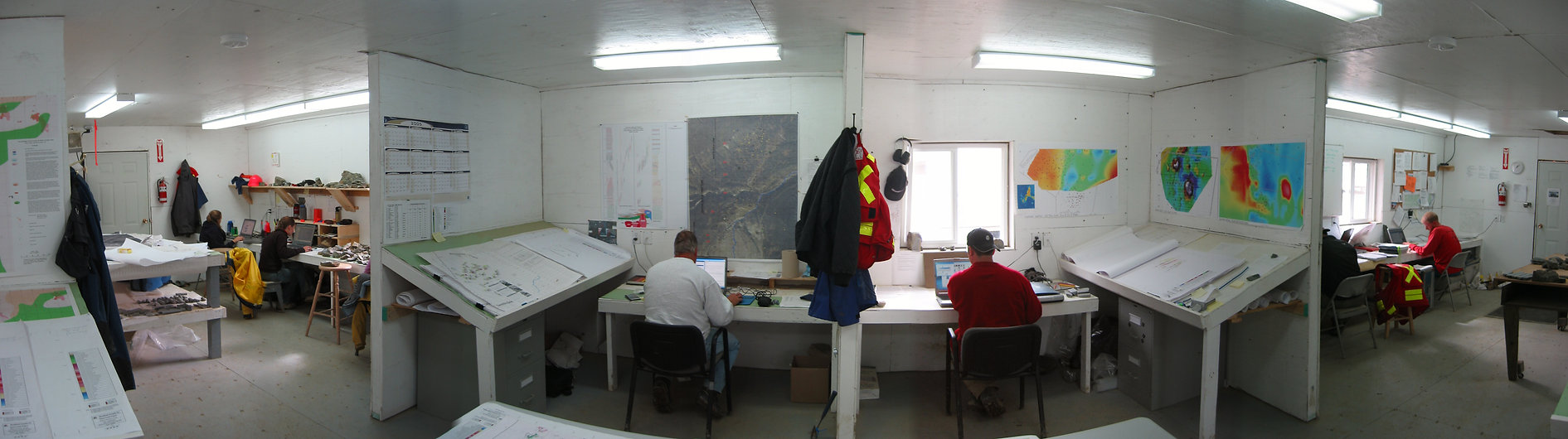 Geologiss in a field office with geophysics and sampling maps on the walls.