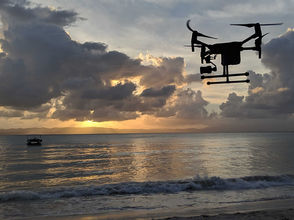 Ethos Geolgocial's drone flying over a Haitian coastline at sunset.