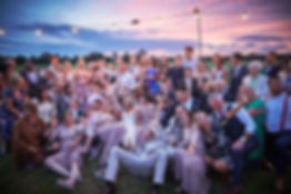 group photo of peopl at sunset at a weddn