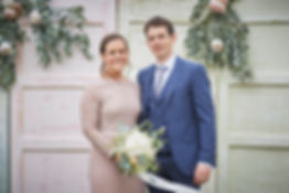 bridesmaid and husband smiling with flowers at a wedding