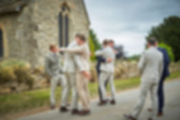 groom, bestmen, bestman and groomsmen hugging ouside of a church on a weddin day
