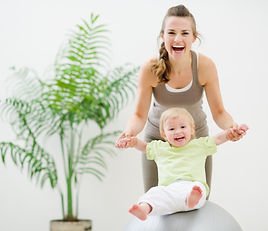 Mother and baby playing with fitness bal
