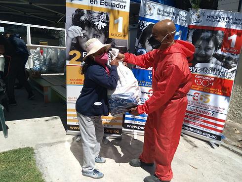 Mitarbeiter Juan Carlos übergibt ein Lebensmittelpaket an eine bedürftige ältere Frau